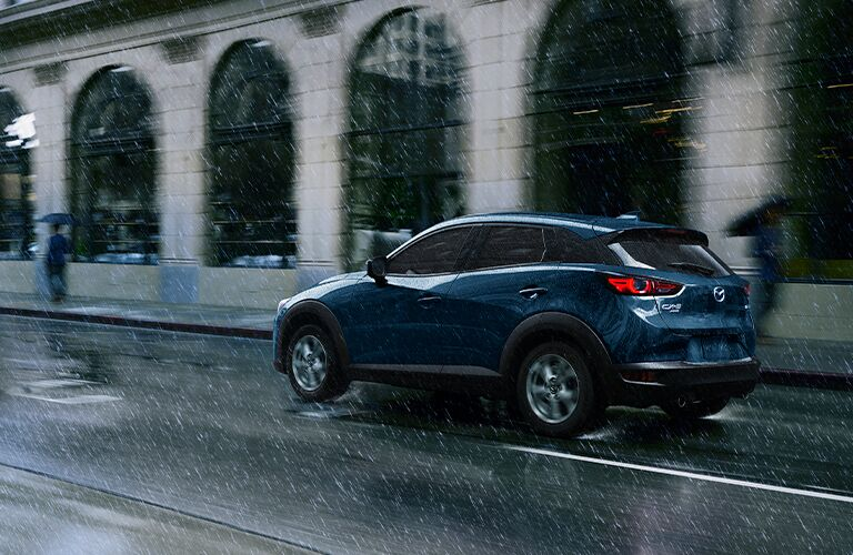 The side and rear view of a blue 2021 Mazda CX-3 driving in the rain.