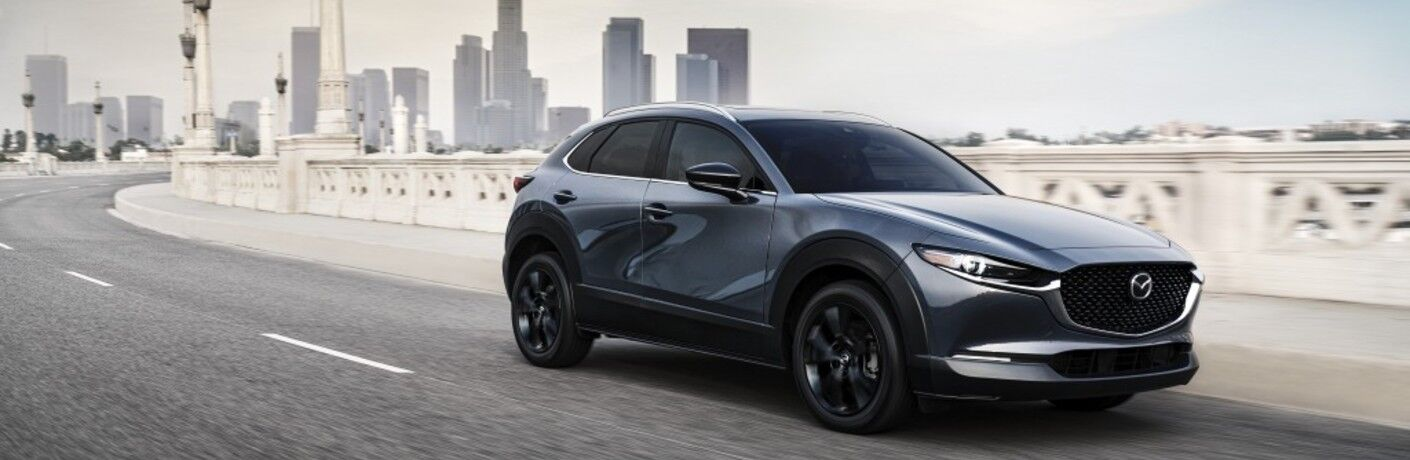 A front and side view of a gray 2021 Mazda CX-30 Turbo model driving away from a city skyline.