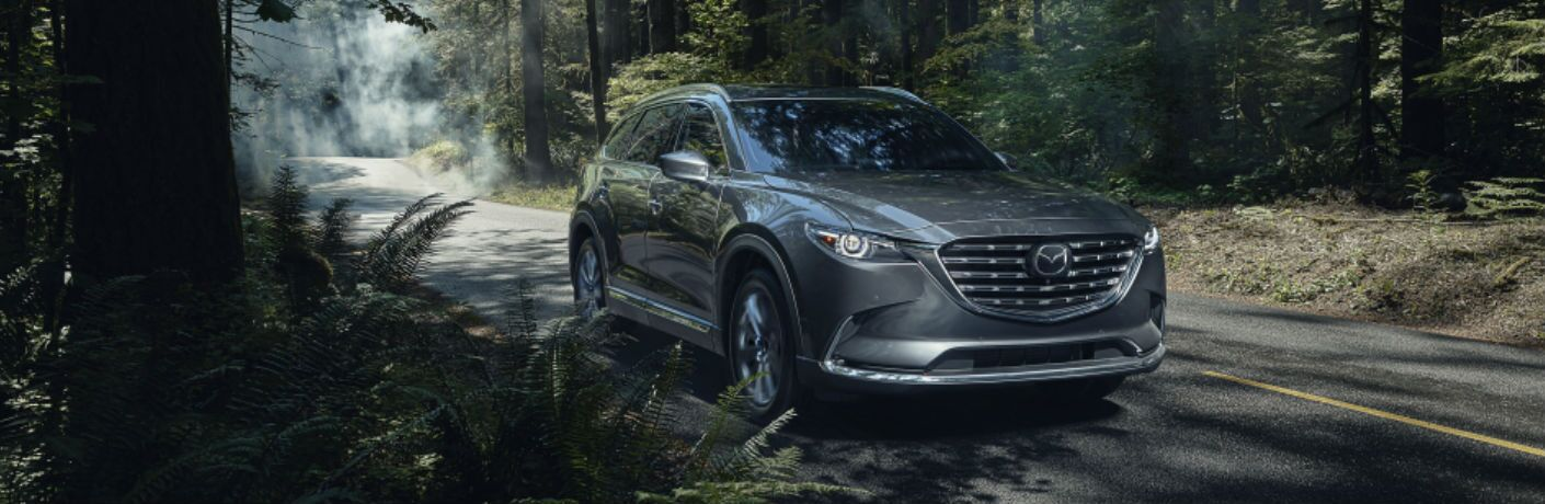 The front and side view of a gray 2021 Mazda CX-9 driving in a forested area.