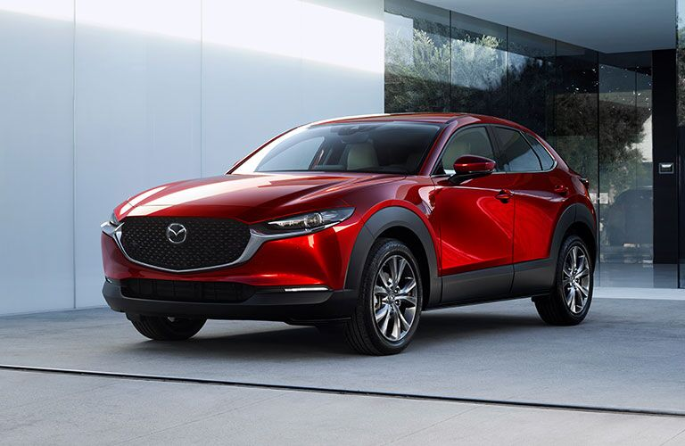 The front of a red 2020 Mazda CX-30 parked in an urban area.