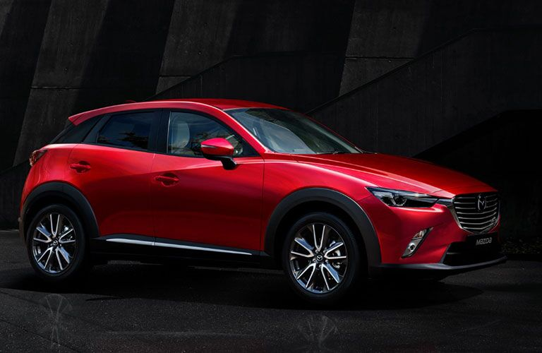 2018 Mazda CX-3 exterior side shot soul red parked in a dark warehouse