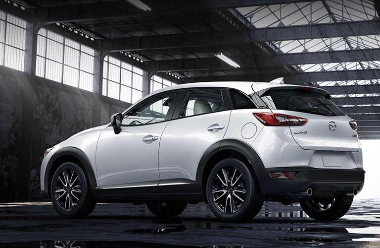 2018 Mazda CX-3 exterior rear shot of side doors, back bumper, and trunk with snow white paint parked in air hangar warehouse