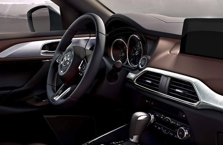 2018 Mazda CX-9 interior shot of front seating, steering wheel, dashboard, and transmission