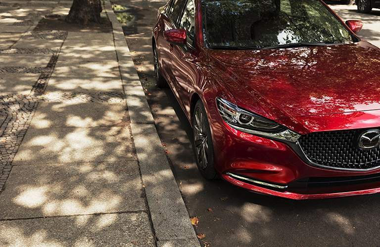 2018 Mazda6 exterior shot red paint job parked on the side of a city street and covered in broken tree shade