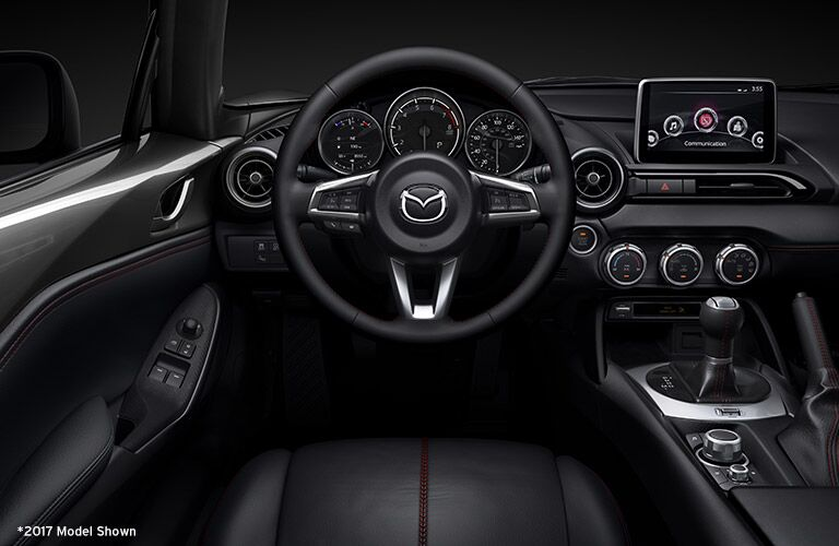 2018 Mazda MX-5 Miata soft top roadster interior driver's view of front seating, steering wheel, and dashboard infotainment