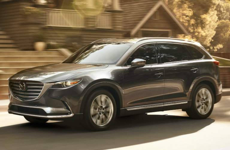 2018 Mazda CX-9 exterior shot driving through a suburban neighborhood bathed in sunlight