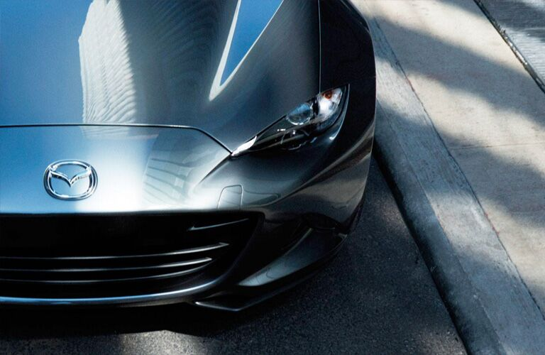 2019 Mazda MX-5 Miata exterior shot closeup of hood badge, grille, and headlight on silver metallic paint color