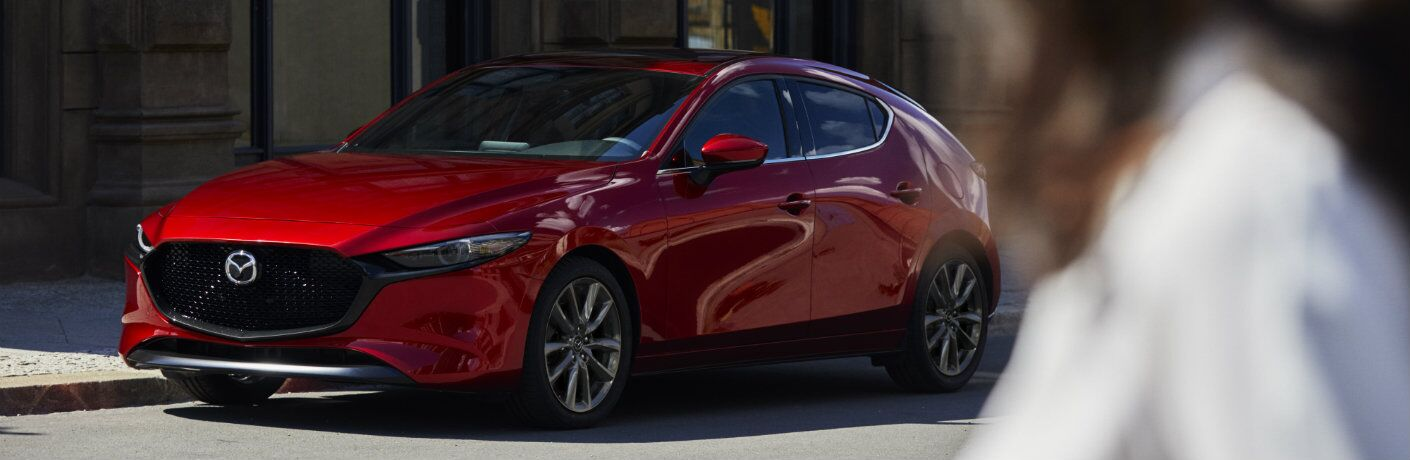 2019 Mazda3 hatchback exterior shot with red paint color parked under the sun as a woman in the foreground stares at it
