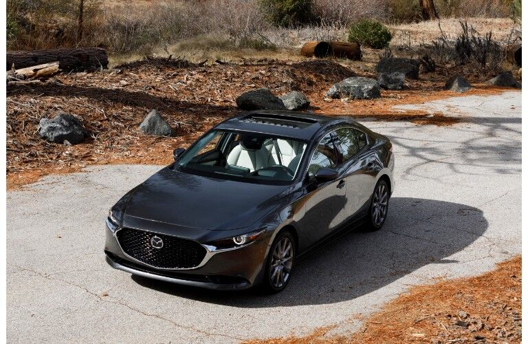 2019 Mazda3 sedan exterior overhead shot with gray metallic paint color parked on a cement path in a bare forest plain