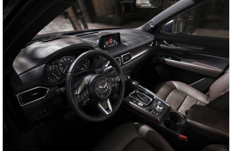 2019 Mazda CX-5 signature trim interior shot of front seating, steering wheel with Mazda badge and dashboard layout with screen and display