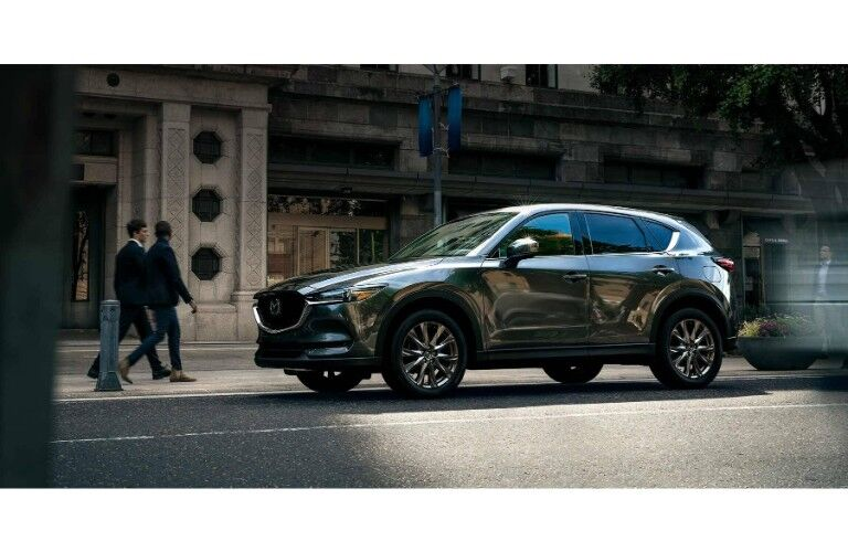 2019 Mazda CX-5 signature trim with gray metallic paint color exterior shot parked near a fancy cafe in an urban city as people walk by