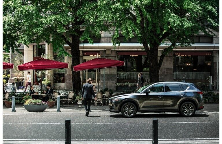 2019 Mazda CX-5 signature trim with gray metallic paint color exterior shot parked near an outdoor cafe with red umbrella and under the shade of green trees
