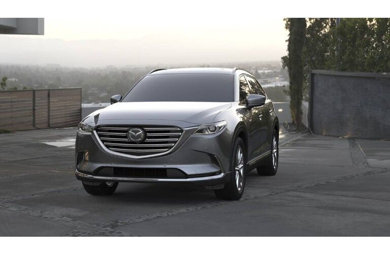 2019 Mazda CX-9 exterior front shot parked on concrete with a city of fog in the background