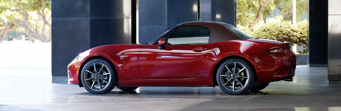 2019 Mazda MX-5 Miata exterior side shot red paint job parked under a roof of metal pillars in a forest
