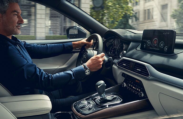 A front seat view of a man driving a 2020 Mazda CX-9.