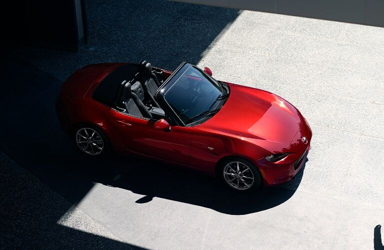 A top and side view of a red 2020 Mazda MX-5 Miata parked in a parking lot.