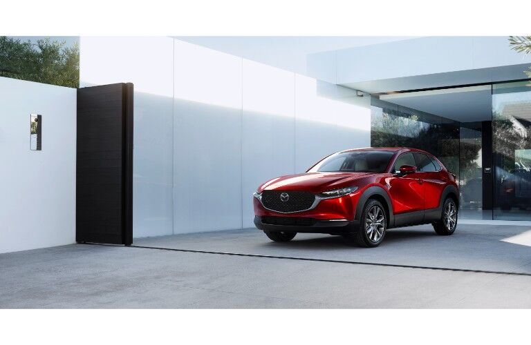2020 Mazda CX-30 compact crossover SUV exterior shot with soul red crystal paint color parked outside a fancy glass house