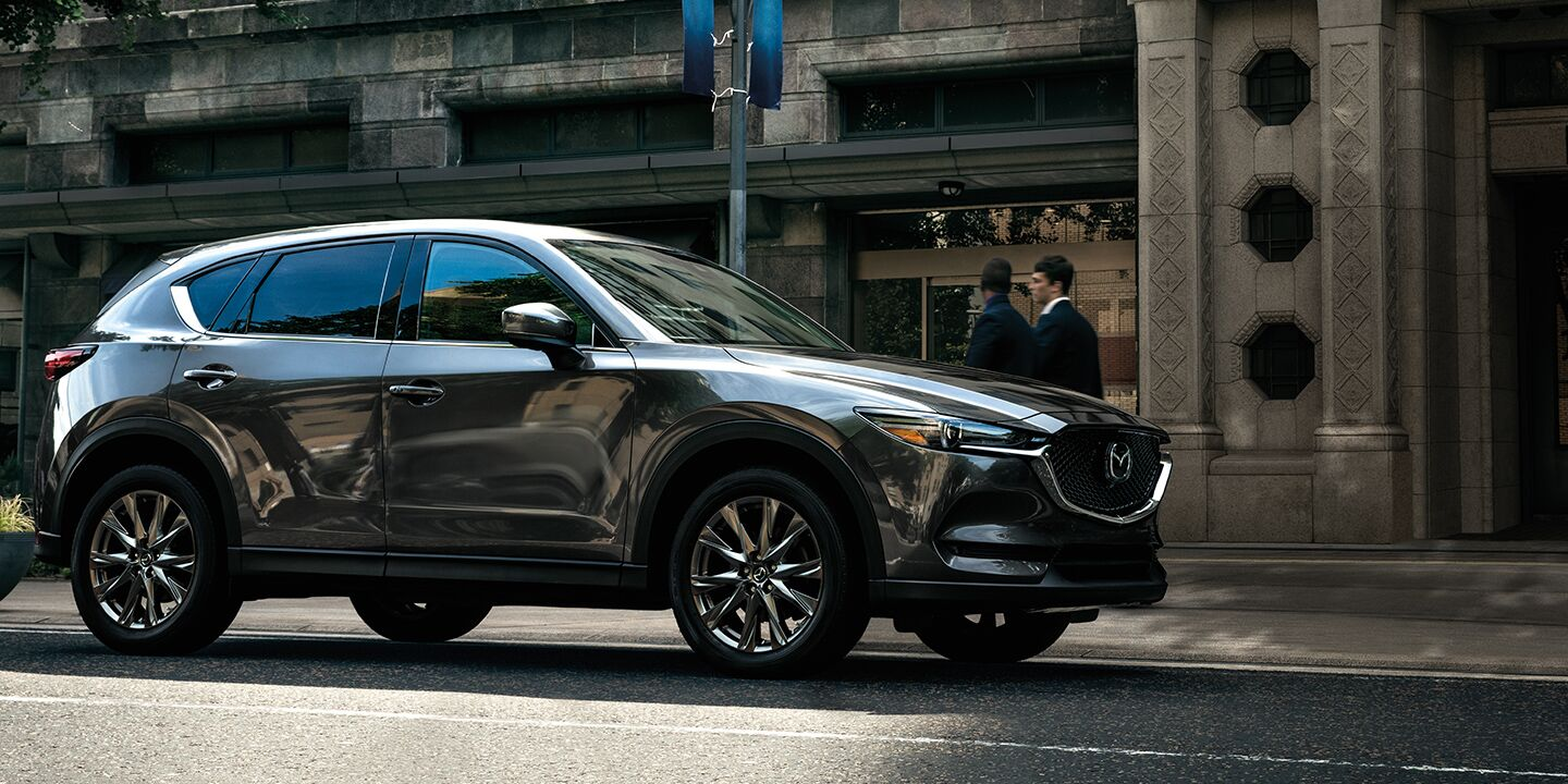 A front and side view of a grey 2020 Mazda CX-5 parked on a street