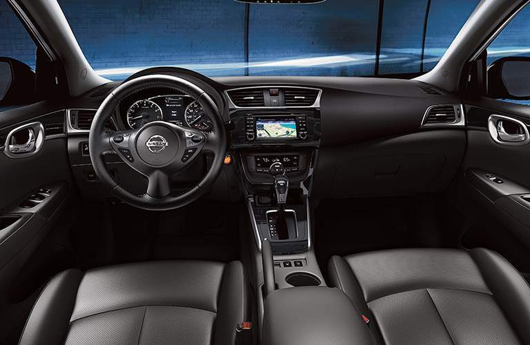 interior of 2018 nissan sentra in black shown with infotainment system and steering wheel on display