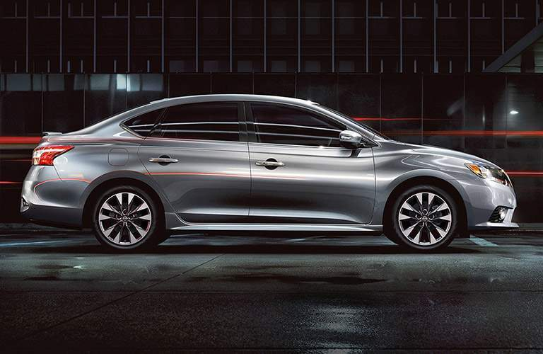 passengers side profile view of 2018 nissan sentra exterior in gun metallic parked in warehouse