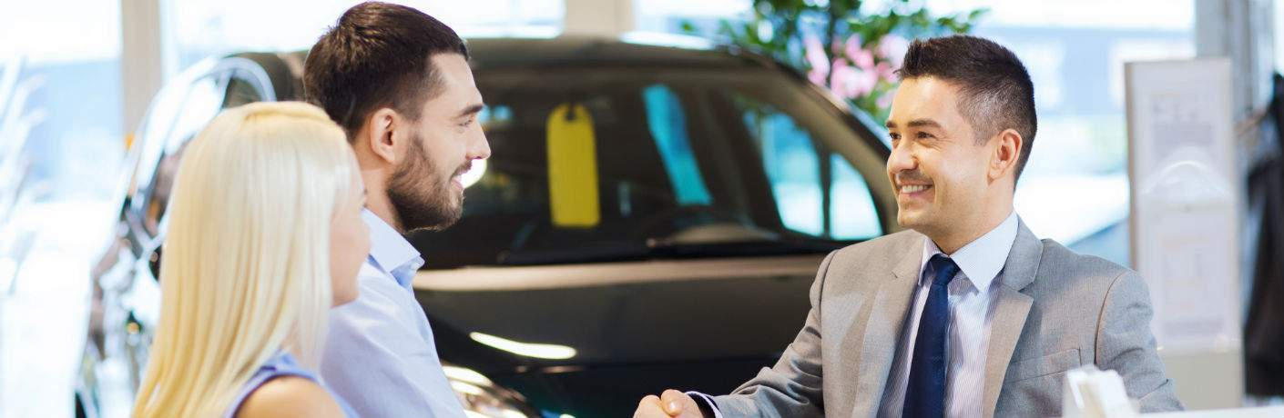car salesman shaking hands with young couple