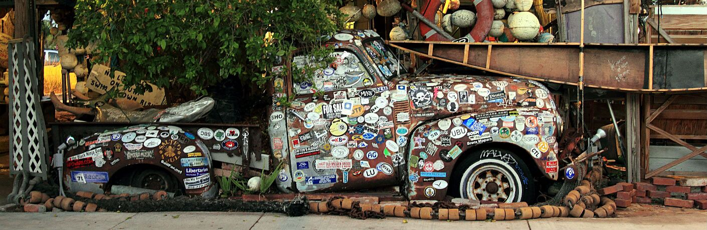 Image of an old truck sitting in the front yard covered in bumper stickers