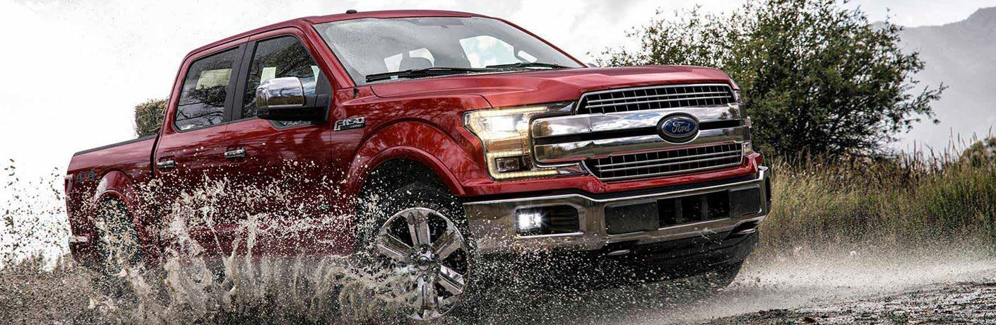 Red 2018 Ford F-150 driving through puddle