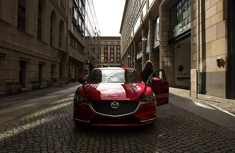 2018 Mazda6 exterior front shot with red paint color parked on a stone tiled road in the middle of a brick city