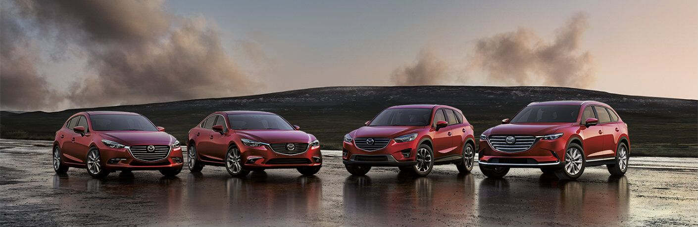 2018 lineup of the Mazda3, Mazda6, Mazda CX-5, and Mazda CX-9 all with red paint color and parked on a wet patch of asphalt