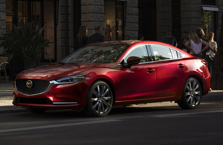2018 Mazda6 midsize sedan exterior shot with soul red paint color parked on the side of a city street outside of a store