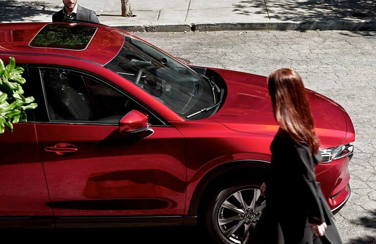 2019 Mazda CX-5 exterior overhead shot with red paint color parked on a city street under the shade of trees as a woman approaches