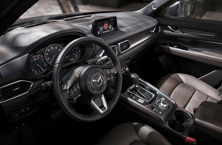 2019 Mazda CX-5 interior shot of front seating, dashboard layout, steering wheel with Mazda badge, infotainment display, and transmission