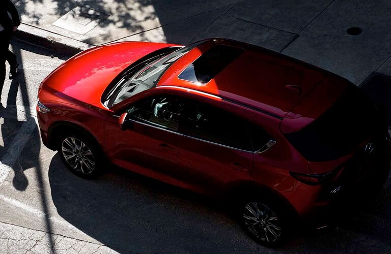2019 Mazda CX-5 exterior overhead shot with red paint color parked on a city street under the shade of trees and buildings