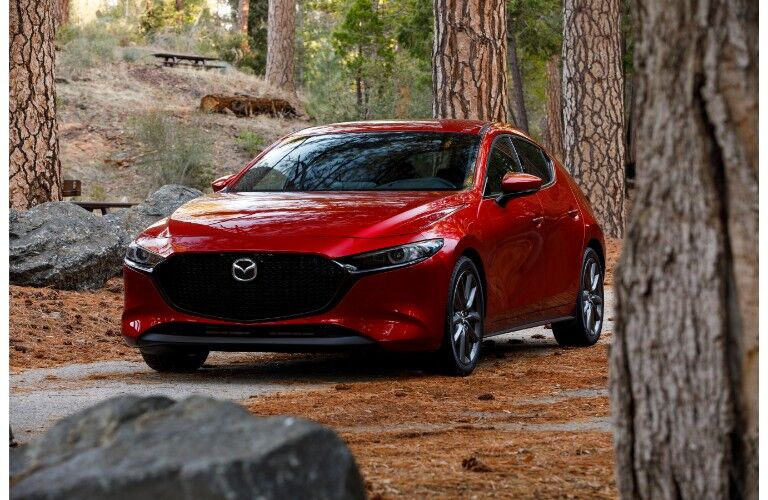 2019 Mazda3 hatchback exterior shot with red paint color parked on a forest raod near hills and tree trunks