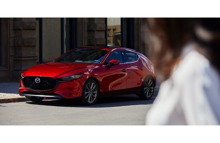 2019 Mazda3 hatchback exterior shot with red paint color parked under the sun with a woman in the foreground staring at it