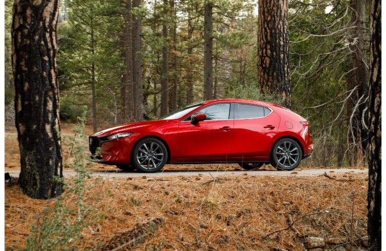 2019 Mazda3 hatchback exterior side shot with red paint color parked on a forest path between a wilderness of brown grass and trees