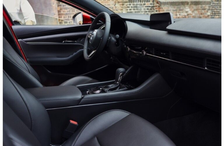 2019 Mazda3 interior side shot of front seating, steering wheel, and dashboard