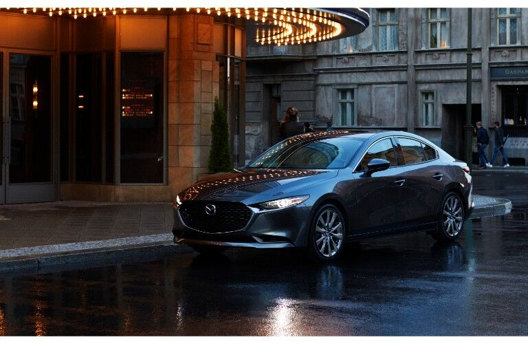 2019 Mazda3 sedan exterior shot with gray metallic paint color parked on a rainy street next to and old world theater