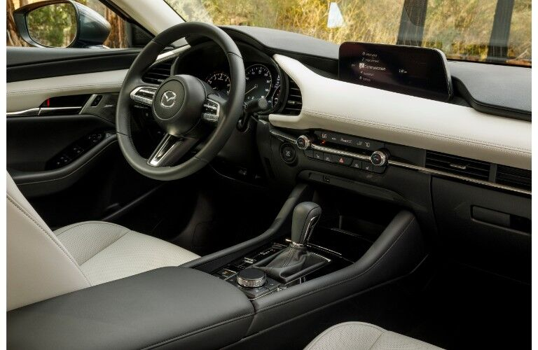 2019 Mazda3 sedan interior shot of dashboard layout, transmission, and steering wheel
