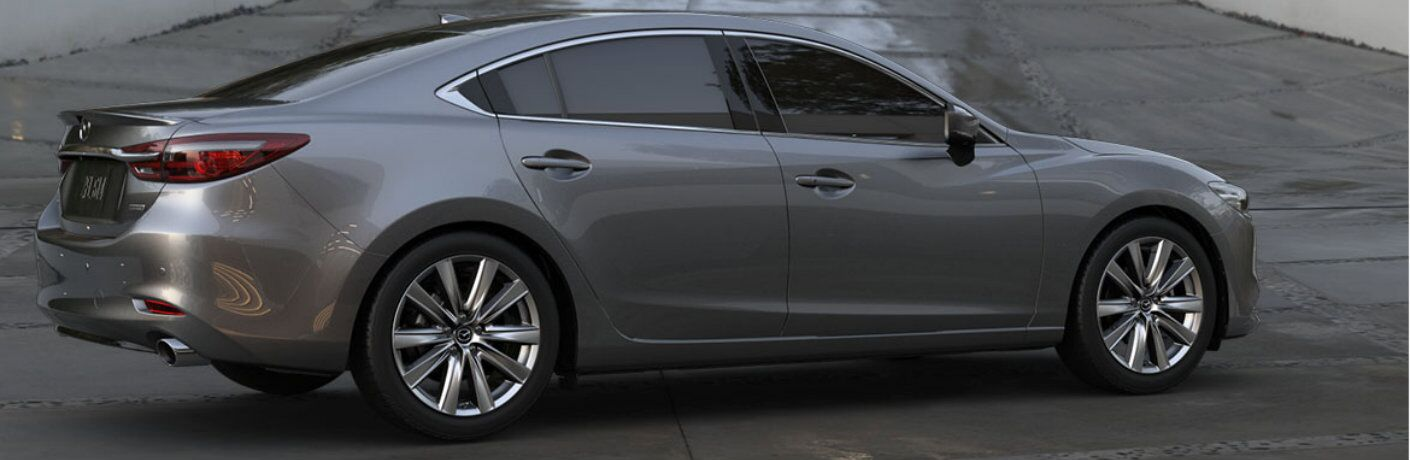 2019 Mazda6 sedan exterior side shot with gray metallic paint color showing back bumper and taillights with a long barrier driveway behind it