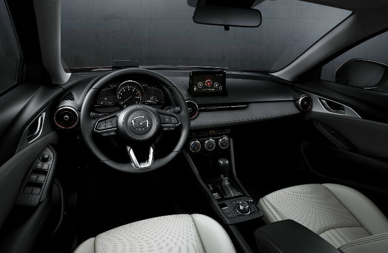 2019 Mazda CX-3 interior shot of front seating, steering wheel, transmission knob, and dashboard display layout
