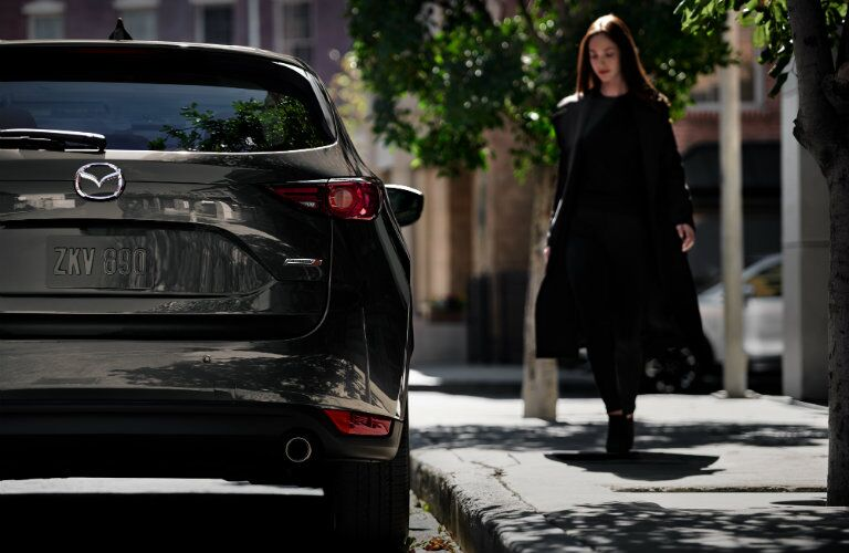 2019 Mazda CX-5 Signature SKYACTIV-D exterior rear shot of back bumper, trunk, and taillights as a woman approaches the passenger side door