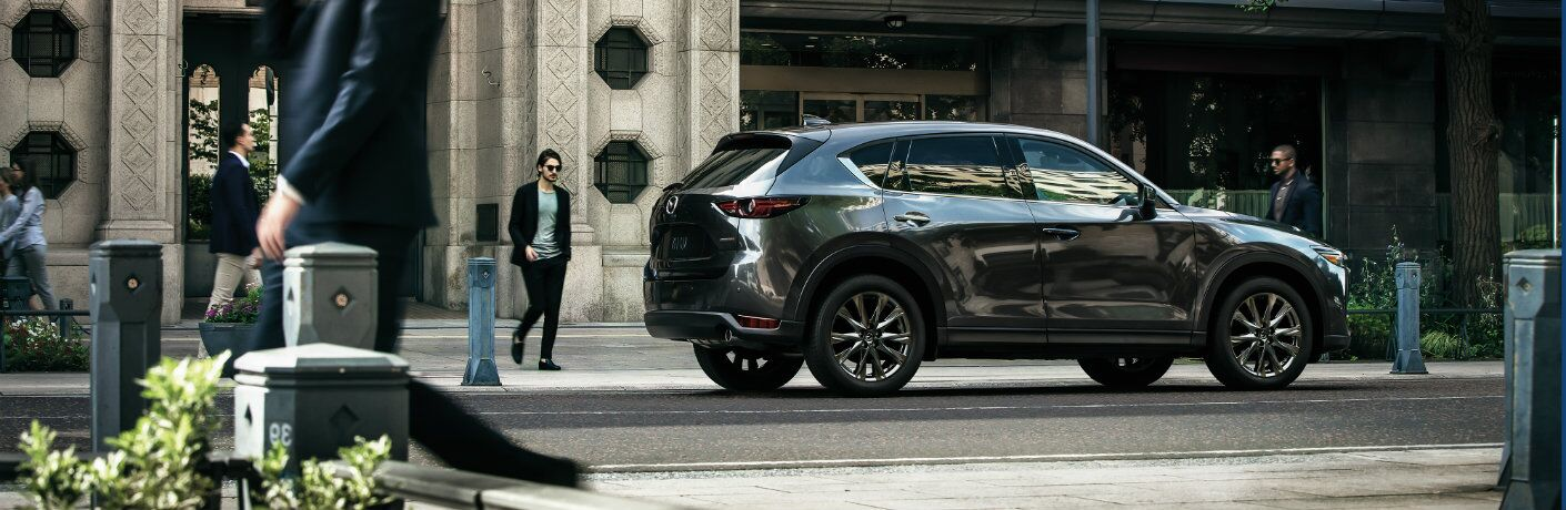 2019 Mazda CX-5 Signature SKYACTIV-D exterior rear shot with gray metallic paint color parked on a city street as pedestrians walk by