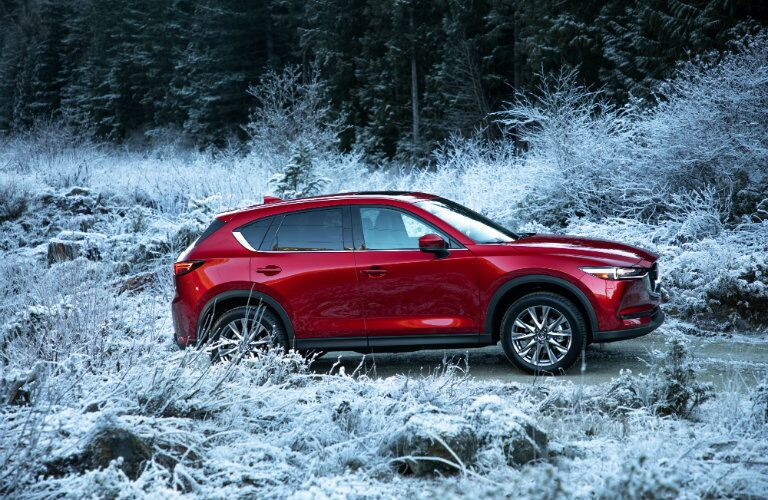 2019 Mazda CX-5 exterior side shot with soul red paint color driving through a snowy field of tall grass and brush