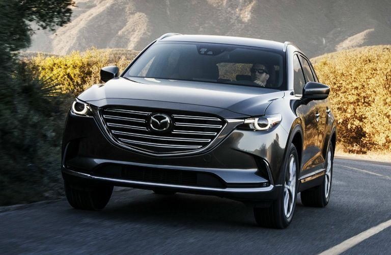 2019 Mazda CX-9 exterior front shot parked in a lot surrounded by high green hedges