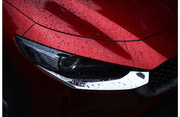 2020 Mazda CX-30 compact crossover SUV exterior closeup shot of new headlight design with a hood sprinkled with rain