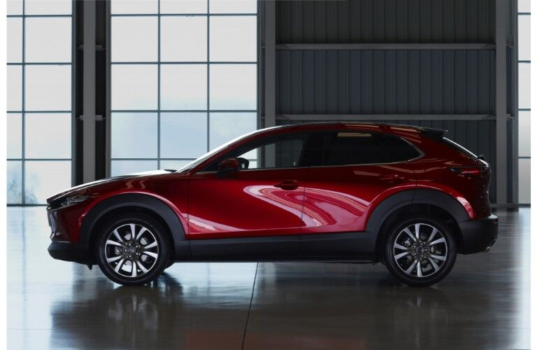 2020 Mazda CX-30 compact crossover SUV exterior side shot in a dark warehouse with light coming from square panel windows