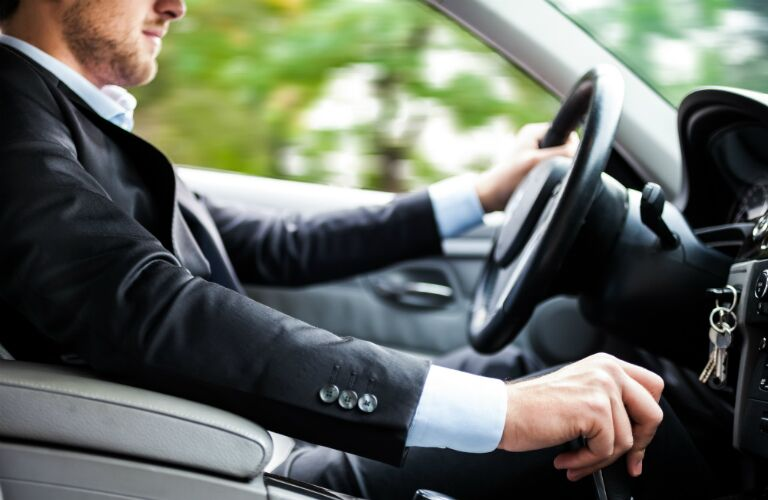 driver driving a manual transmission sedan