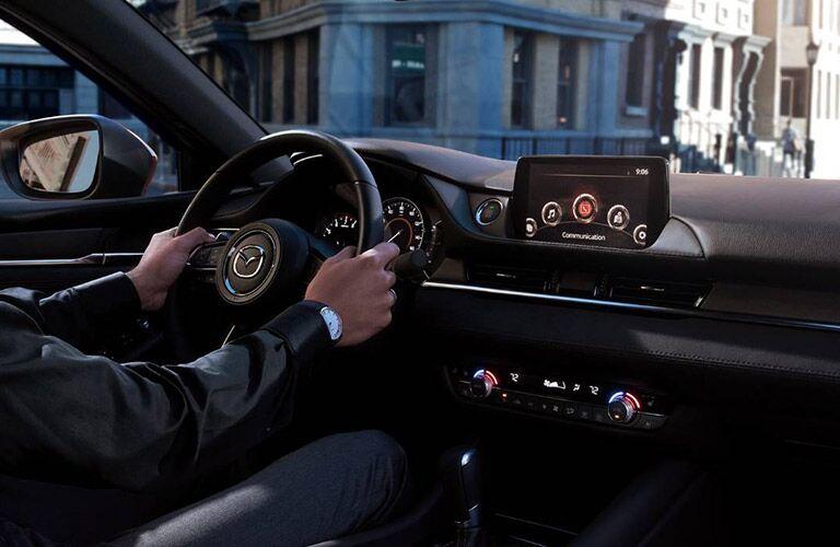 cockpit of mazda3, driver's hands on wheel