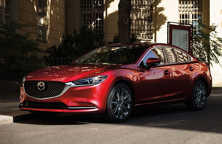front view of red mazda6 parked on side of city street